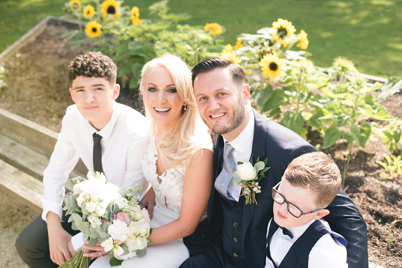 bride and groom with kids in cliff at lyons at summer wedding