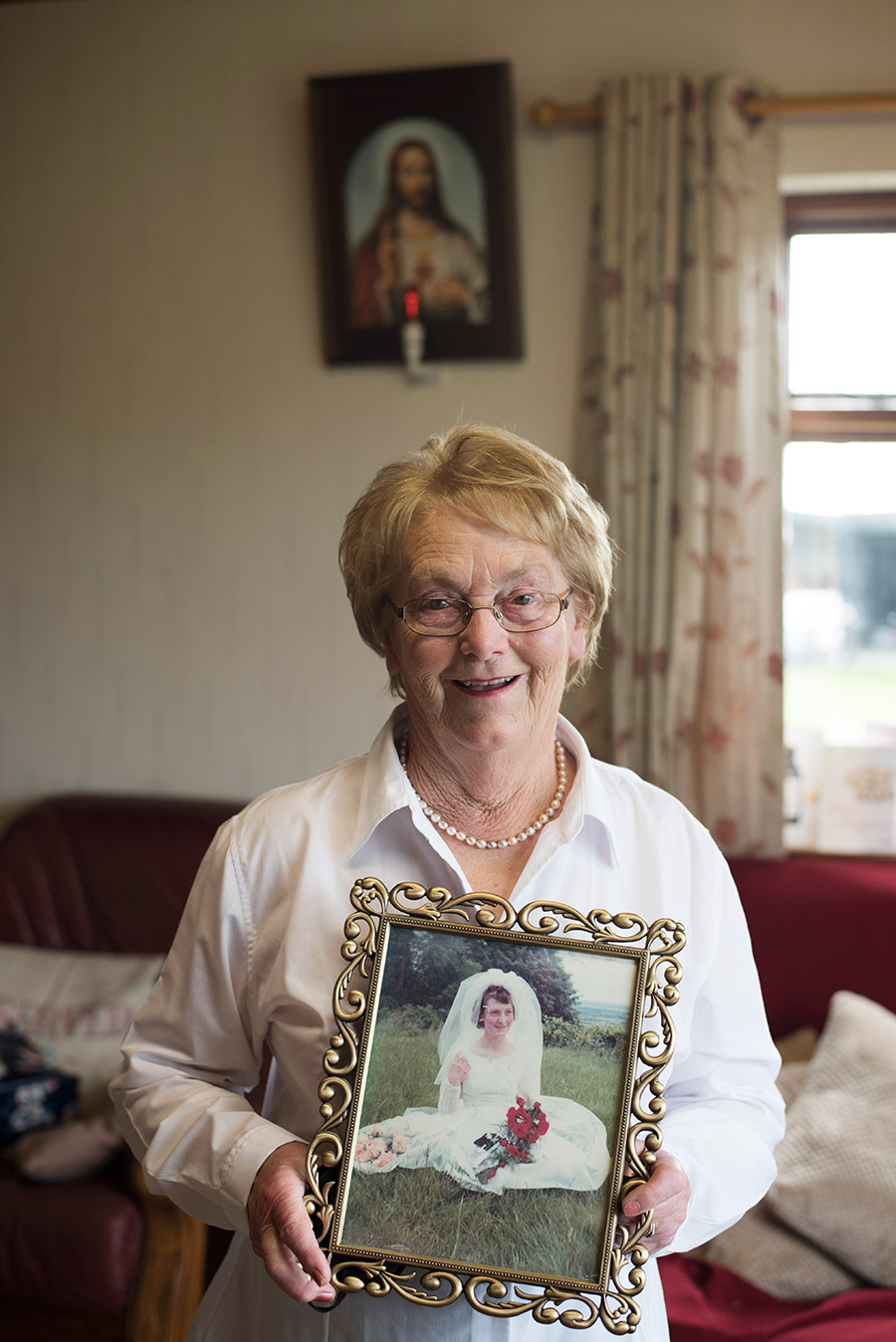 Irish mother of the bride holds her wedding photo