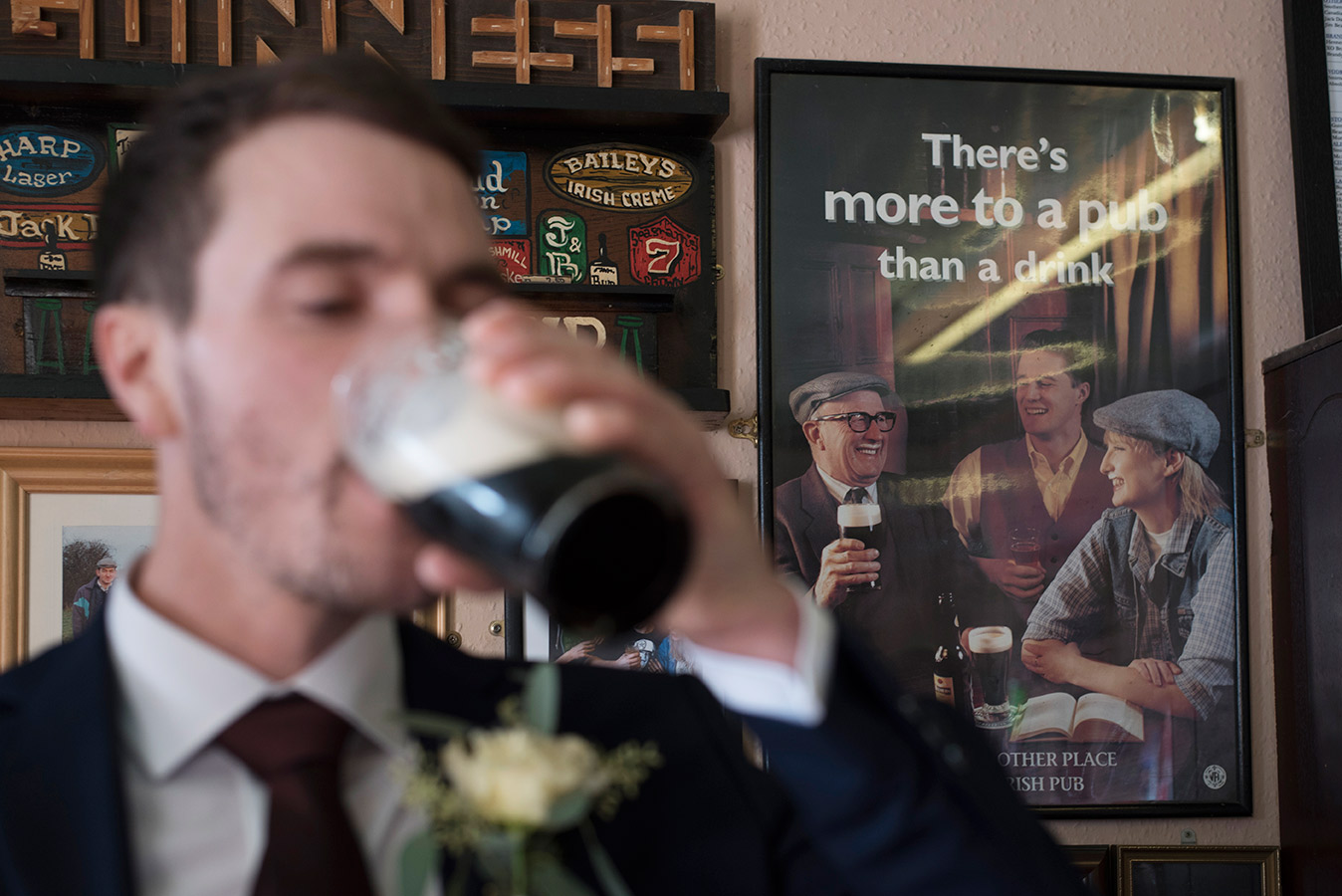 groom drinks guinness in pub on wedding day