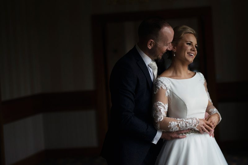 bride and groom hug in windowlight at knightsbrook hotel wedding