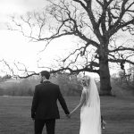 bride and groom walk to rathsallagh tree black and white wedding photo