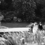 bride and groom walk in gardens of druids glen over lake