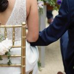 close up bride and groom outdoor wedding ceremony holding hands