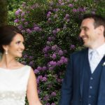 bride and groom stand in front of colourfull flowers at brooklodge wedding