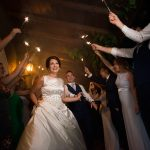 bride and groom surrounded by sparklers wedding nighttime photo