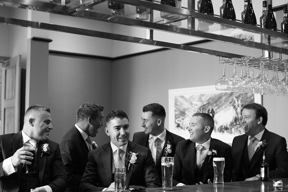 groomsmen enjoying a pint at the bar at summer wedding at druids glen hotel