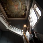 the bride and groom and their sons walk down the grand staircase at luttrellstown castle wedding